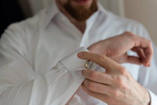 Weißes Hemd mit Umschlagmanschette und vergoldetem Perlmutt-Manschettenknopf.
