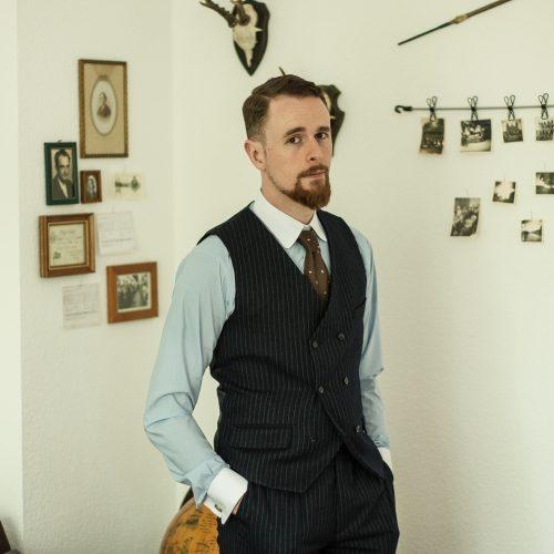 Hellblaues Hemd mit weiß abgesetzten Manschetten und Kragen. Darüber dunkelblaue Hose und zweireihige Weste mit Nadelstreifen.