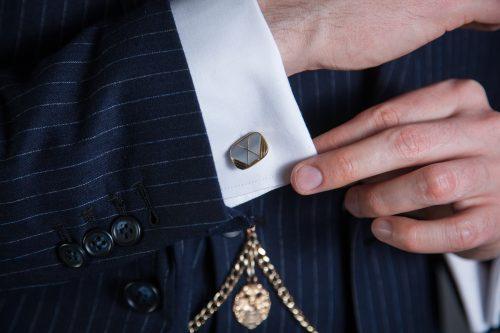 Nahaufnahme einer weißen Hemdmanschette mit vergoldetem Perlmutt-Manschettenknopf.