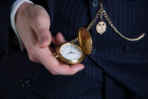 Nahaufnahme einer vergoldeten Taschenuhr mit Taschenuhrkette (Double-Albert).