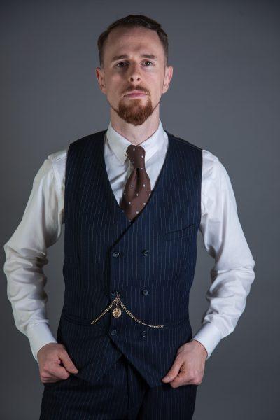 Outfitbeispiel der Mode der Zwanziger Jahre. Weißes Hemd, Paisley-Krawatte, Krawattennadel, zweireihige Weste.