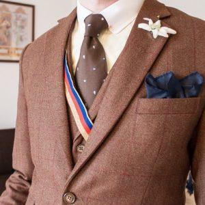 Brauner Dreiteiler aus Tweed mit rotem Überkaro. Paisley-Krawatte, Edelweiß im Knopfloch, dunkelblaues Einstecktuch und Alanen-Band.