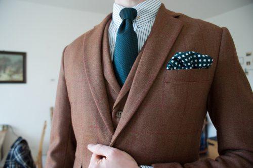 Outfitbeispiel mit braunem Dreiteiler aus Tweed mit rotem Karo, gestreiftes Hemd, Krawattennadel, Krawatte aus grüner Seidengrenadine, dunkelblau-grünes Einstecktuch mit weißen Kästchen.