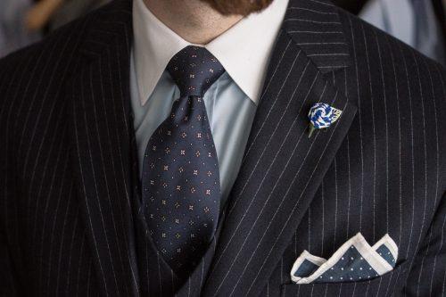 Dunkelblauer Nadelstreifenanzug mit dunkelblauer Seidenkrawatte, blau-weißem Einstecktuch und weiß-blauer Couleurrose
