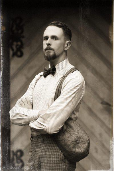 Beispiel für 20er-Jahre-Outfit mit Hosenträgern, Schiebermütze und Fliege.