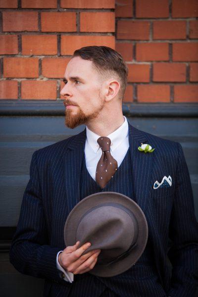 Dunkelblauer Nadelstreifen-Anzug mit Boutonniere, Einstecktuch und Fedora (Hut)