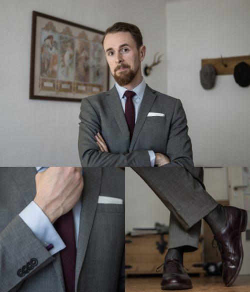 Low Budget Outfit mit grauem Anzug, hellblauem Hemd, weißem Einstecktuch und weinroter Krawatte.