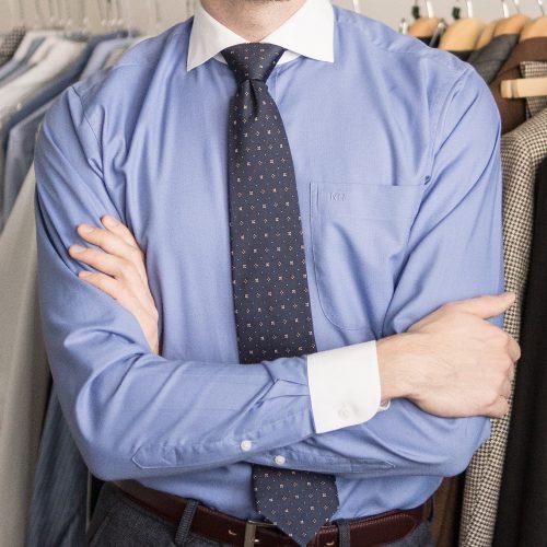Blaues Hemd mit weißem Haifischkragen und weißen Manschetten. Dunkelblaue Krawatte mit Muster.