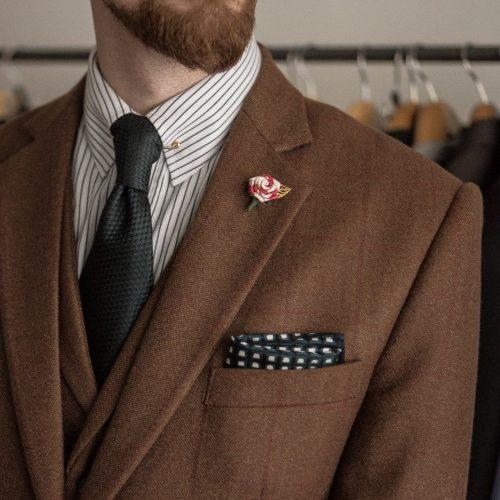 Rotbraunes Tweedjackett, wei0es Hemd mit schwarzen Streifen, dunkelgrüne Krawatte aus Seidengrenadine.