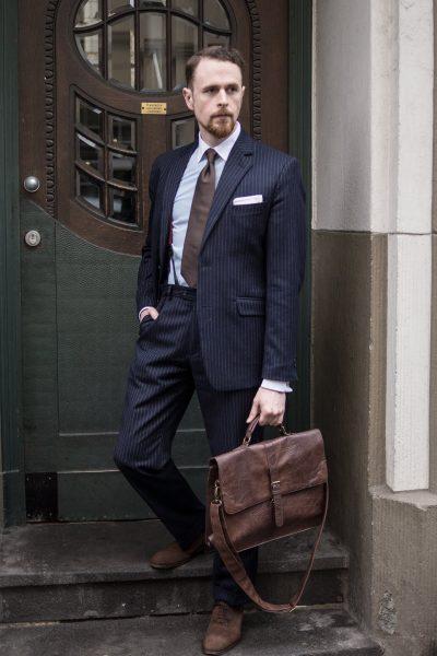 Dunkelblauer Nadelstreifen-Anzug mit Raulederschuhen, Aktentasche und Krawatte in Dunkelbraun.