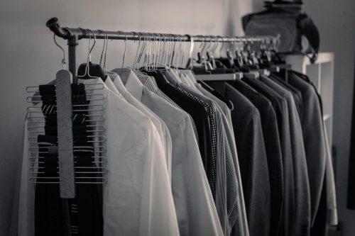 Offene Garderobe aus Industrie-Rohr voll mit Hemden und Anzügen.