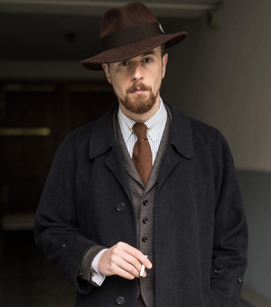 Brauner Fedora, dunkler Mantel, brauner Anzug