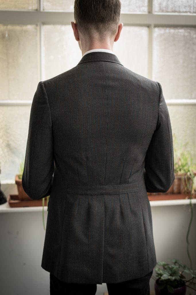 Die Rückseite des Jacketts mit langem Mittelschlitz und eingenähtem Gürtel.