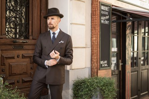 Zweireihiger Anzug aus feiner, dunkelbrauner Wolle mit braunem Homburg.