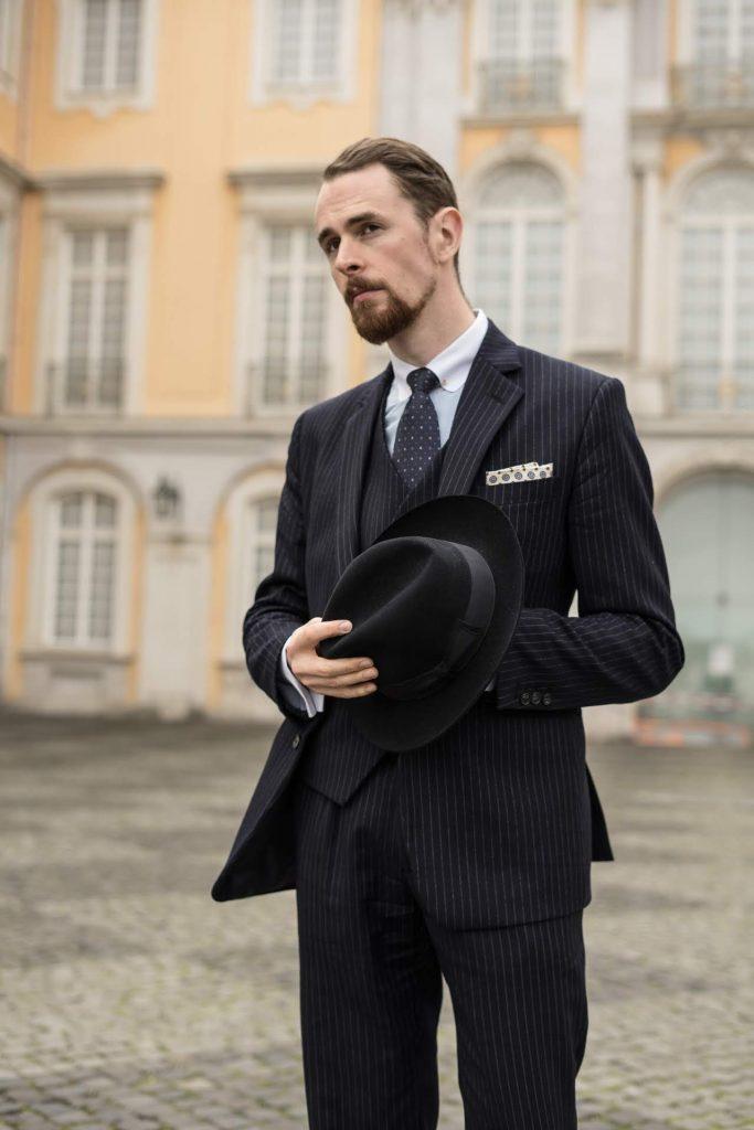 Dunkelblauer Nadelstreifen-Anzug von Hockerty mit hellblauem Hemd, weißem Kragen, dunkelblauer Krawatte und cremefarbenem Einstecktuch.