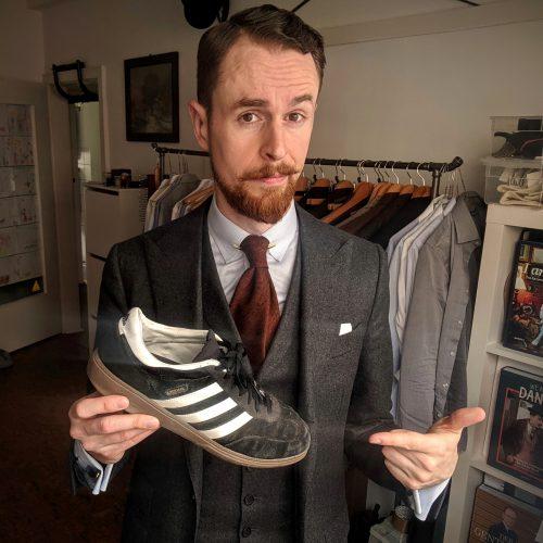 Mit typischem Adidas-Sneaker in der Hand
